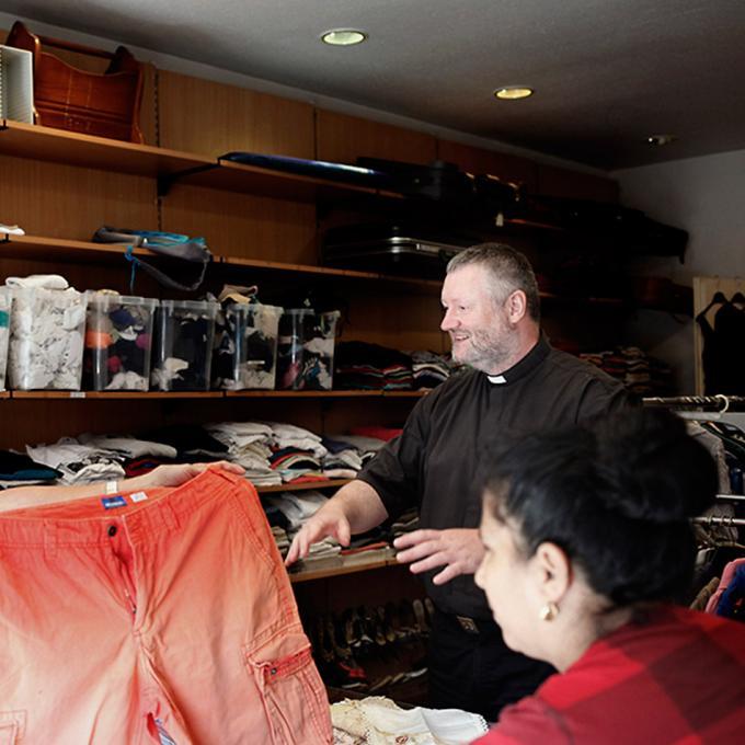 Pater Oliver und Mitarbeiterinnen in der Kleiderkammer
